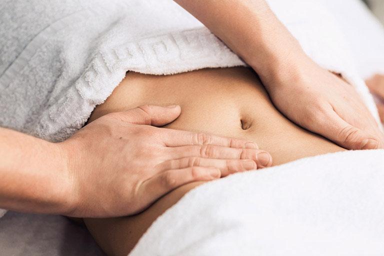 Xoa nhẹ vùng bụng với dầu nóng cũng giảm cơn đau khá hiệu quả